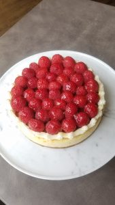 Whole vanilla cheesecake topped with raspberries
