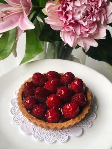Raspberry chocolate tart on a white plate, in front of pink flowers