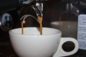 Double shot of espresso pours from a portafilter into an ivory cup.