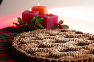 Raspberry Linzer torte with red candles and sprigs of holly