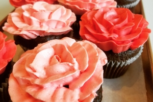 Chocolate Valentine's Day cupcakes frosted with pink and red buttercream flowers.
