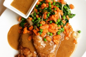 Pork schnitzel with gravy, spring peas, and red pepper spaetzle on a white plate.