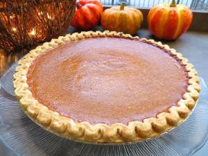 Pumpkin pie in front of small decorative pumpkins.