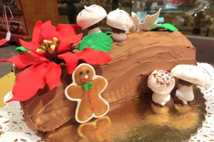 Christmas Yule log (Buche de Noel) decorated with sugar poinsettia and meringue mushrooms.