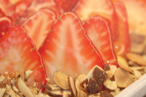 Close-up of strawberry custard tarts garnished with sliced almonds.