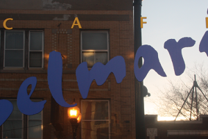 Lincoln Avenue reflected in Cafe Selmarie's window, in Lincoln Square.