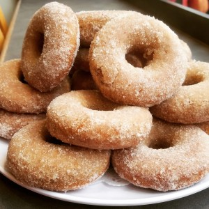 Cinnamon sugar donuts stacked on a white plate.