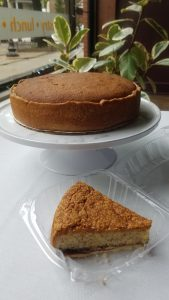 Since of rustic almond cake in front of whole rustic almond cake