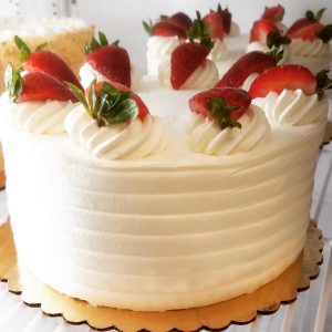 Whole tres leches cake, frosted with whipped cream and topped with strawberries