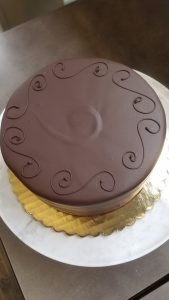 Whole Sacher torte, glazed with dark chocolate, on a marble cake stand