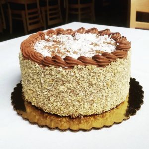 Whole German chocolate cake, topped with coconut, on a white tablecloth