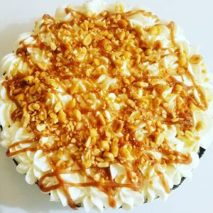 Overhead view of whole pie covered with whipped cream, caramel, and peanuts