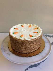 Whole carrot cake topped with candy carrots on a marble cake stand