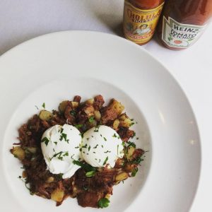 Bowl of corned beef hash topped with poached eggs, and ketchup and hot sauce bottles