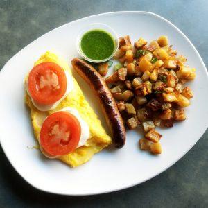 Scrambled eggs, sliced fresh mozzarella, two tomato slices, one sausage, sauteed breakfast potatoes, and a small ramekin of pesto