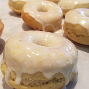 Tray of baked lemon donuts covered with lemon icing