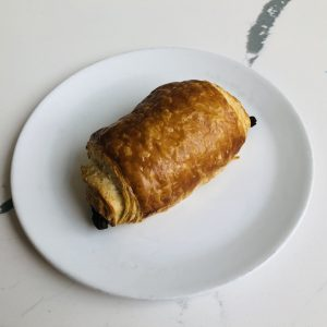Overhead view of chocolate croissant on white plate