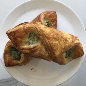 Overhead view of white plate with two spinach ricotta croissants