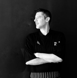 Chef Gide Merriman stands with his arms folded against a dark wall, with his face turned away from the camera.